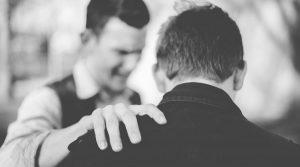 man praying with other man